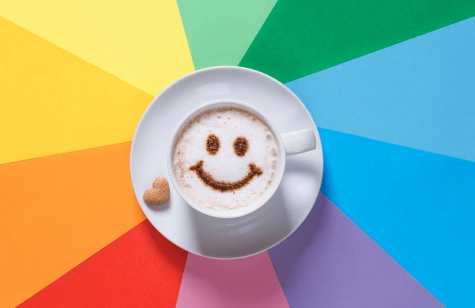 A cup of coffee with a smiley face dusted on top sits on a rainbow background