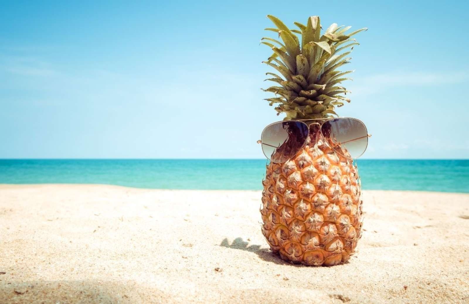 Pineapple wearing subglasses on a sunny beach