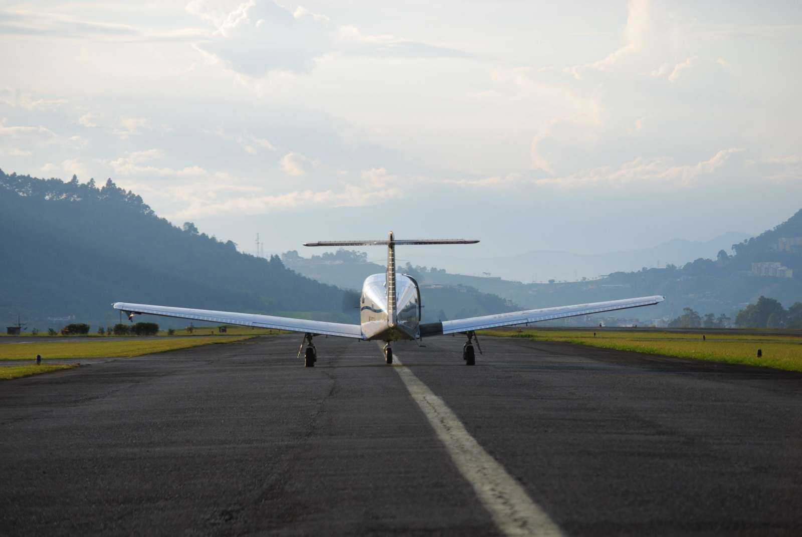 A shiny chrome airplane gets ready to launch into flight on a runway. The runway is surrounded by bright green grass and a beautiful mountainscape is in the background, in the direction the plane is taking off into.