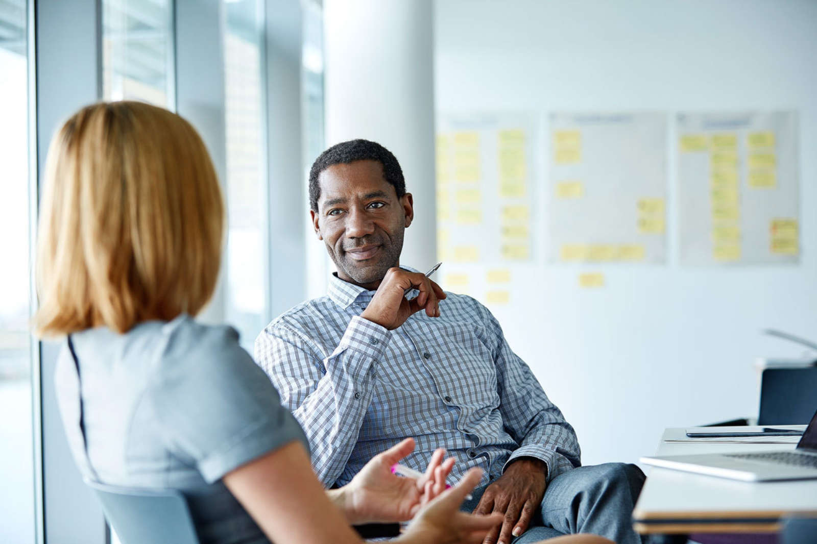 Career coach meets with client in office setting business discussion.jpg