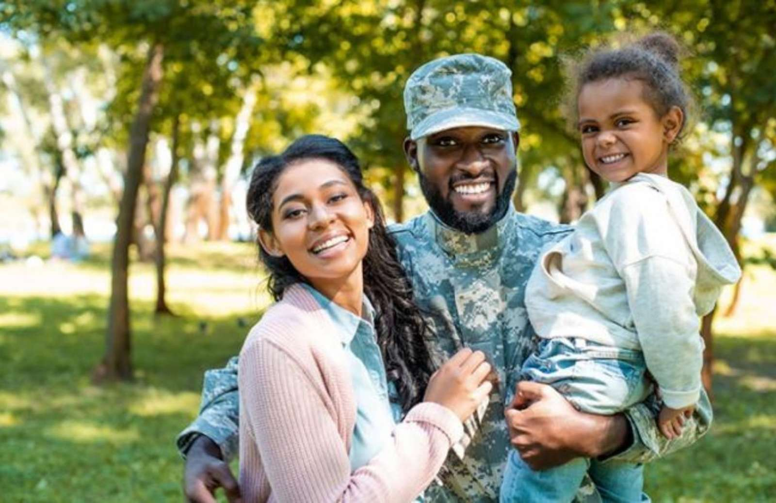Man in miltary fatigues holding child with arm around spouse