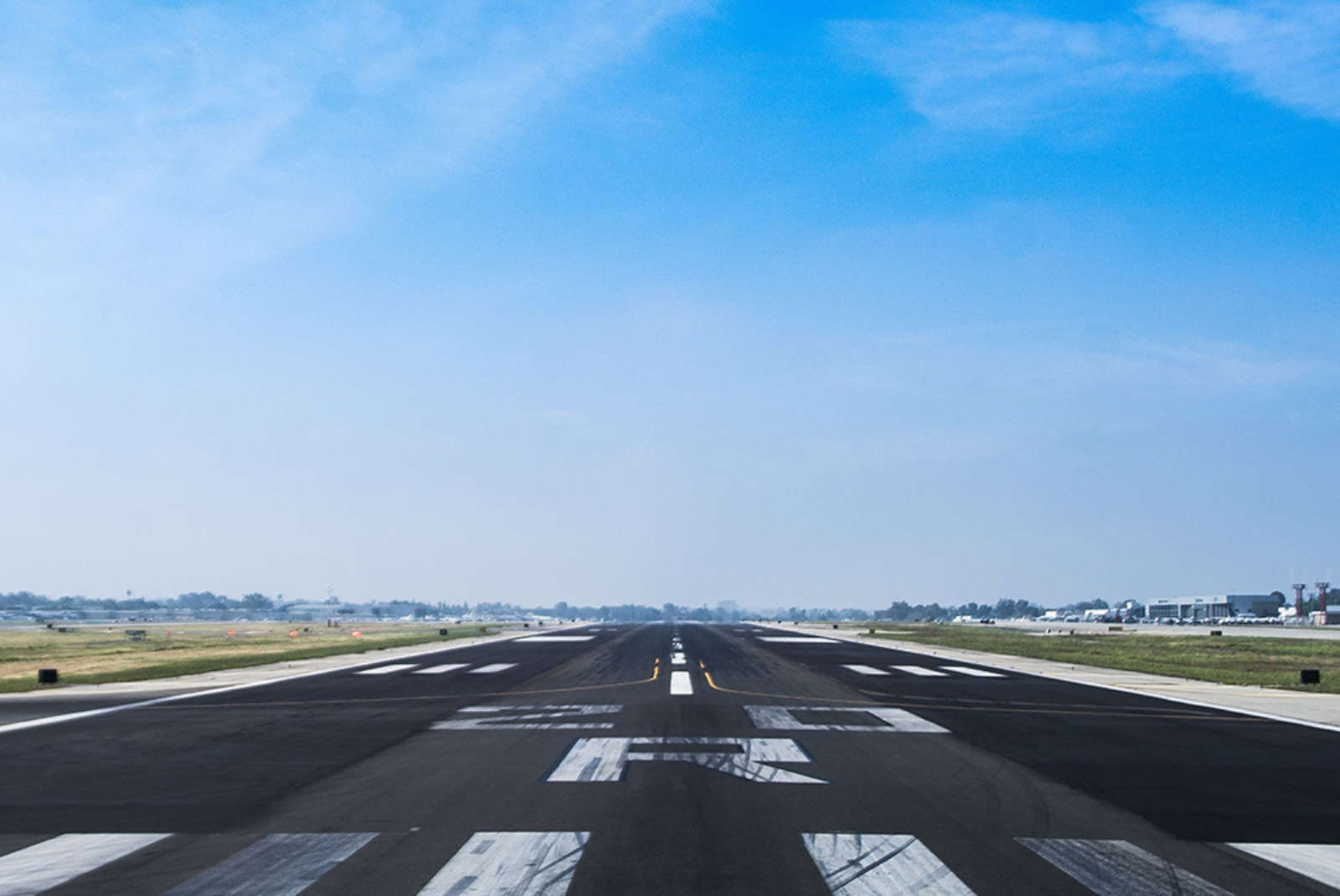 Underneath a bright blue sky, an airplane runway leads off into the horizon, providing a space to land.