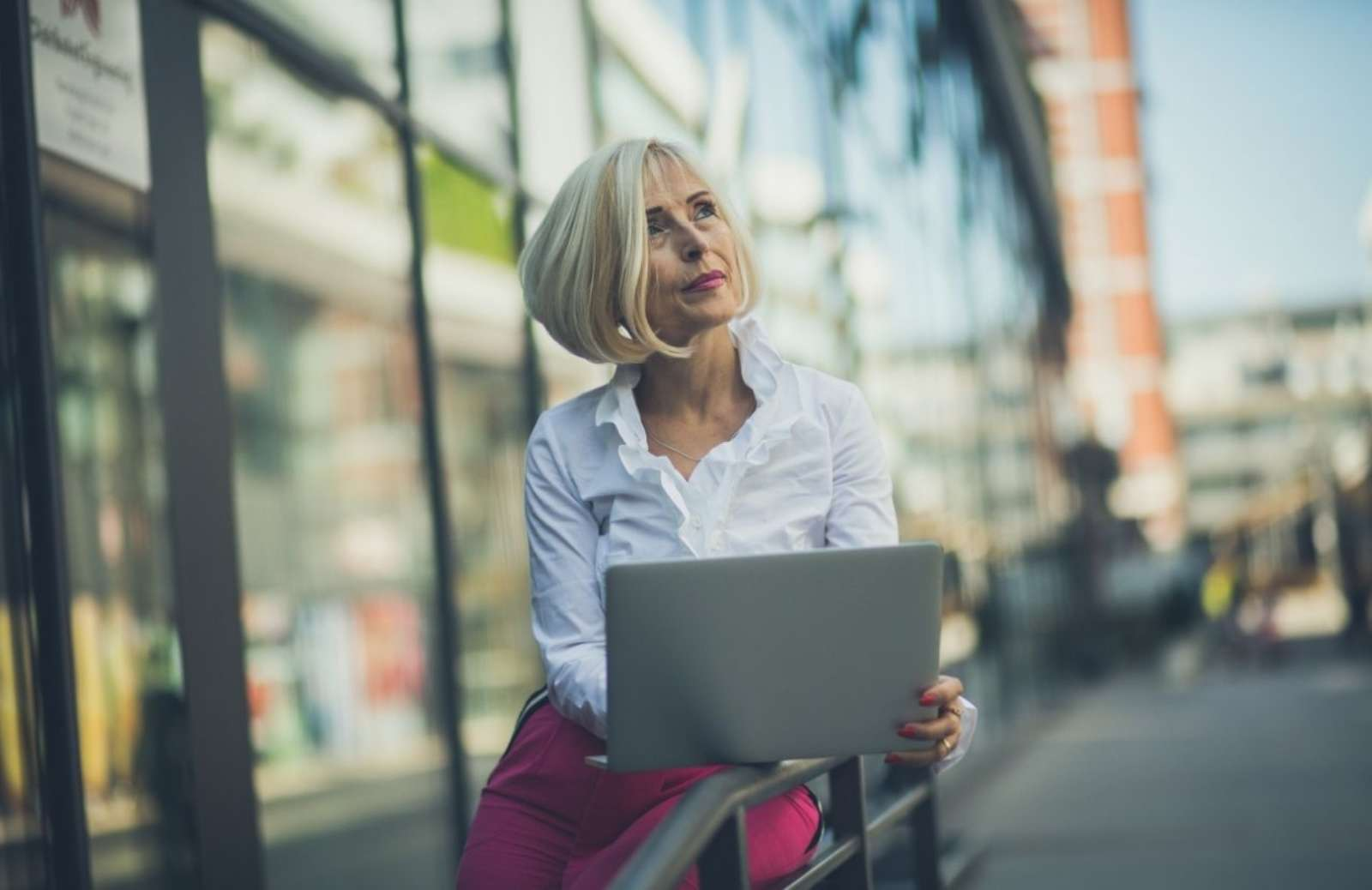 Woman sitting outside, holding laptop, looking off into distance