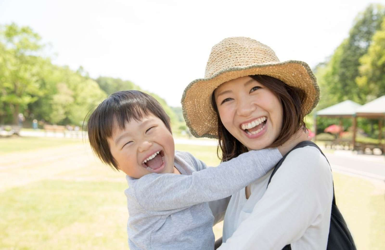 Asian woman smiling while holding smiling son