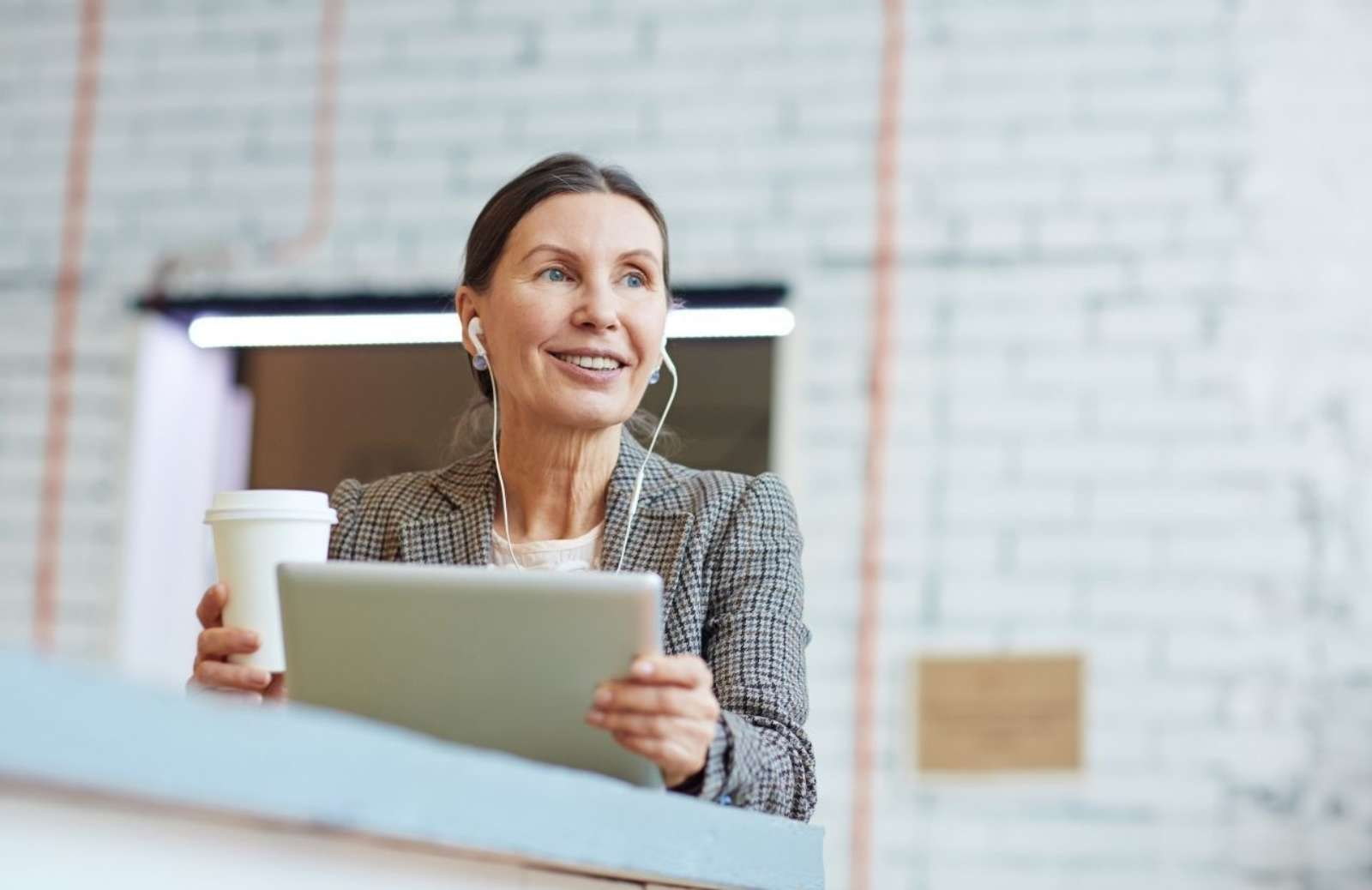 Woman wearing earphones, holding coffee cup and laptop computer screen