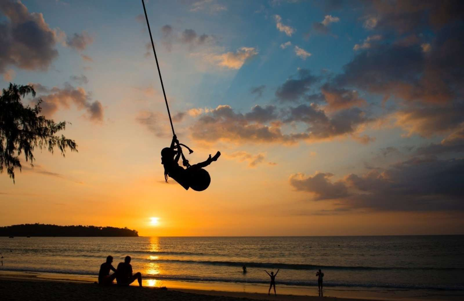 A summer sun sets over a body of water. Silhouettes of a family, lounging, playing and swinging on a rope are on the shoreline.