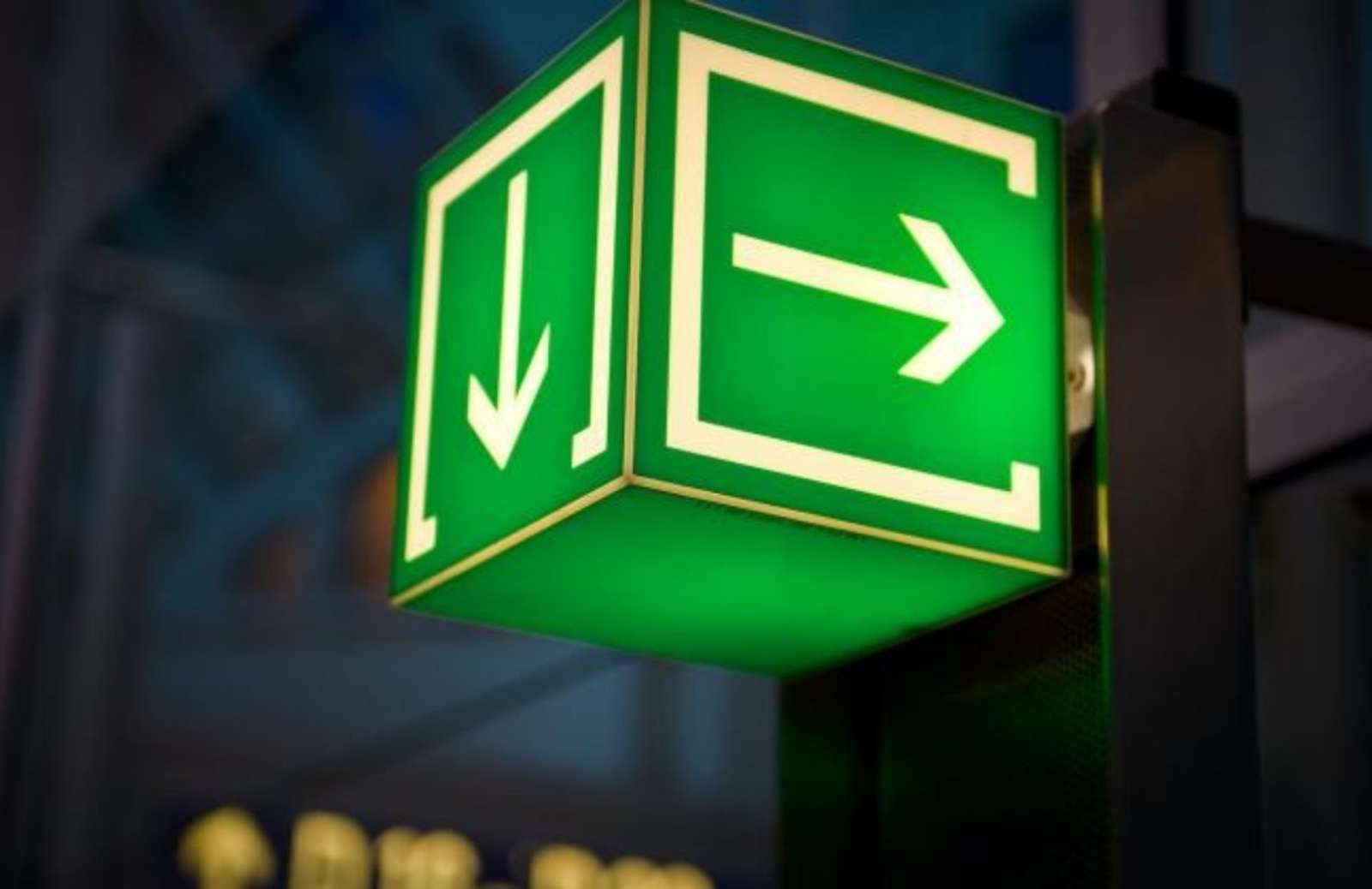 Green neon sign with white arrows pointing right and down