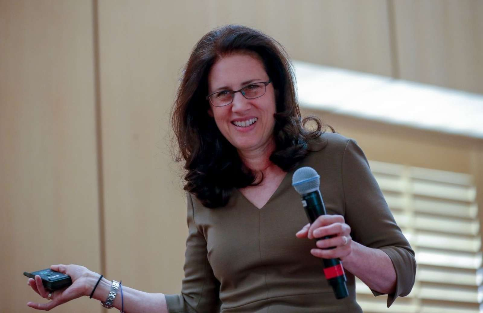 iRelaunch CEO and Co-Founder Carol Fishman Cohen holding microphone and smiling