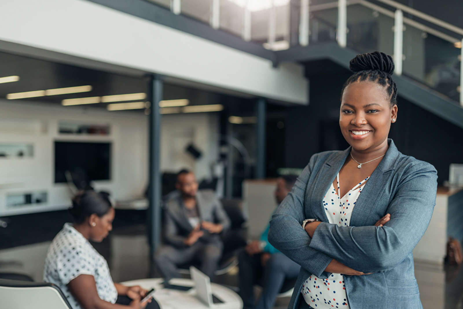 Confident business woman crosses arms smiling at camera in office with coworkers behind her