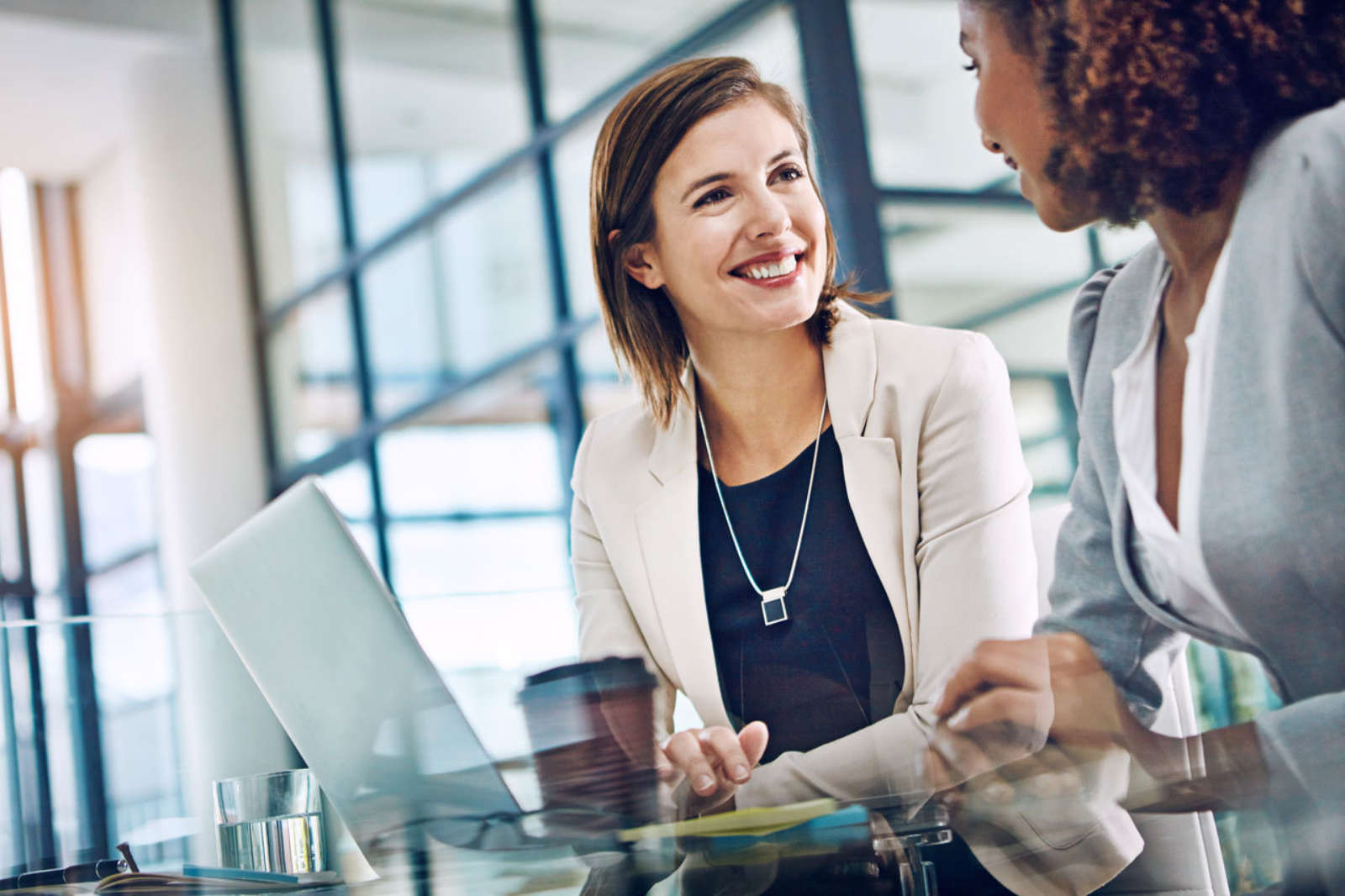 Confident woman smiles at colleague at work effective productive collaboration meeting