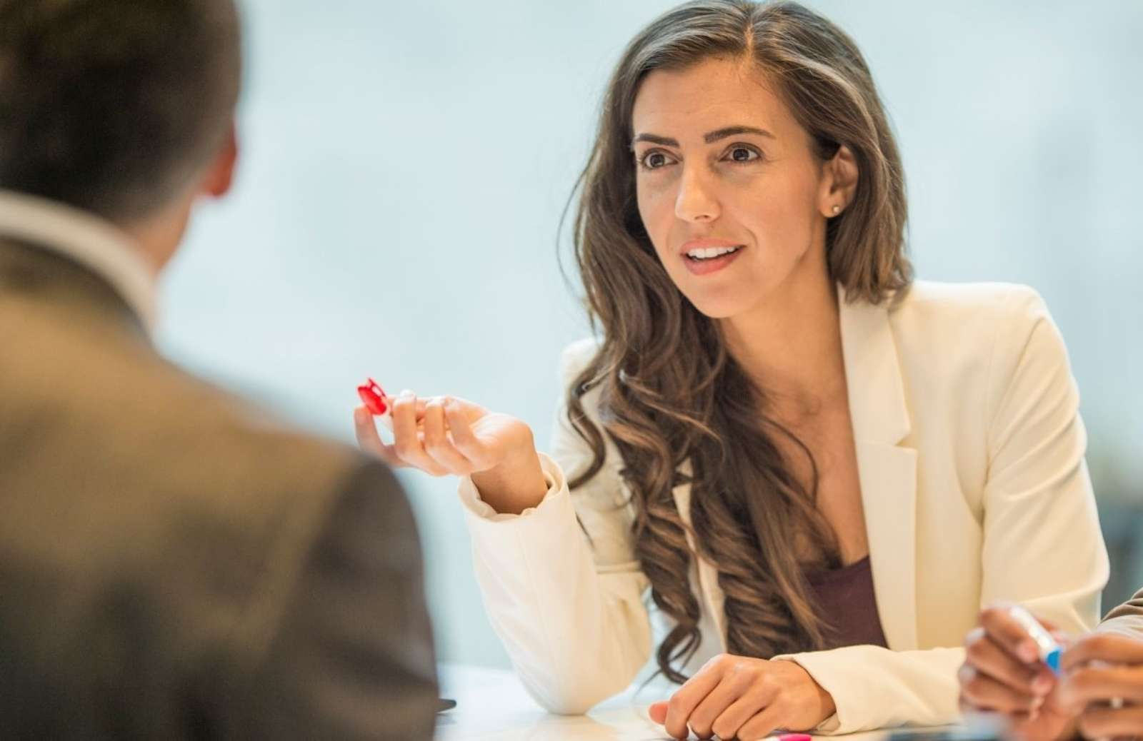 Business woman sitting at desk speaking and gesturing to man