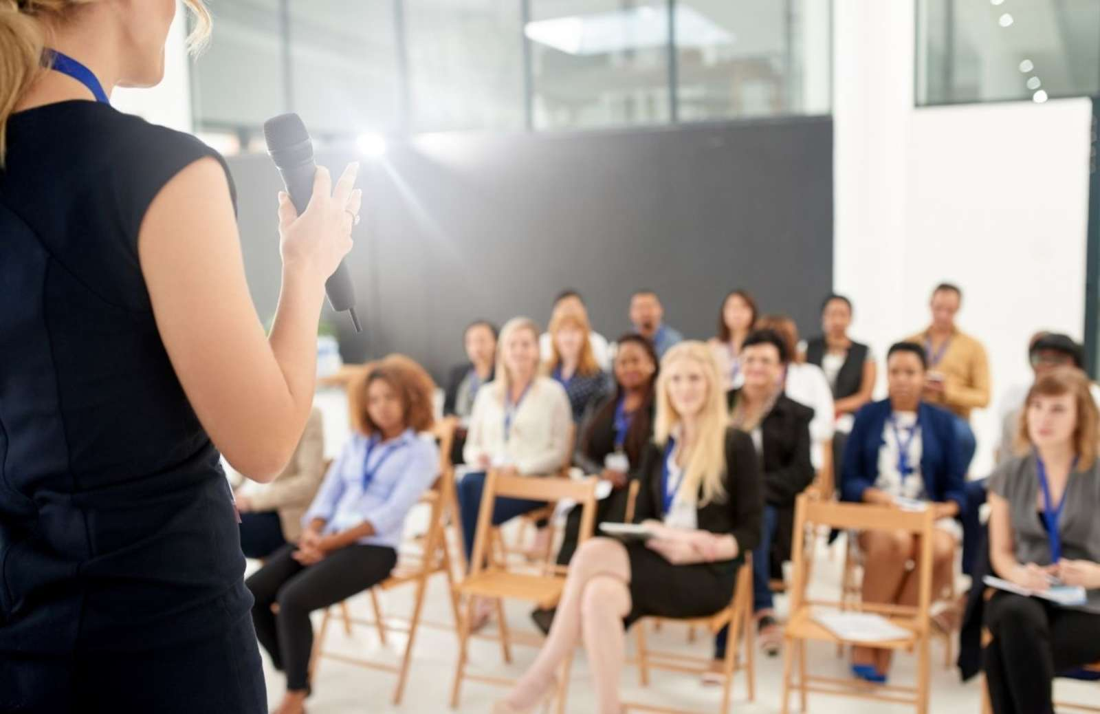 Woman teaching class full of adult students at desks