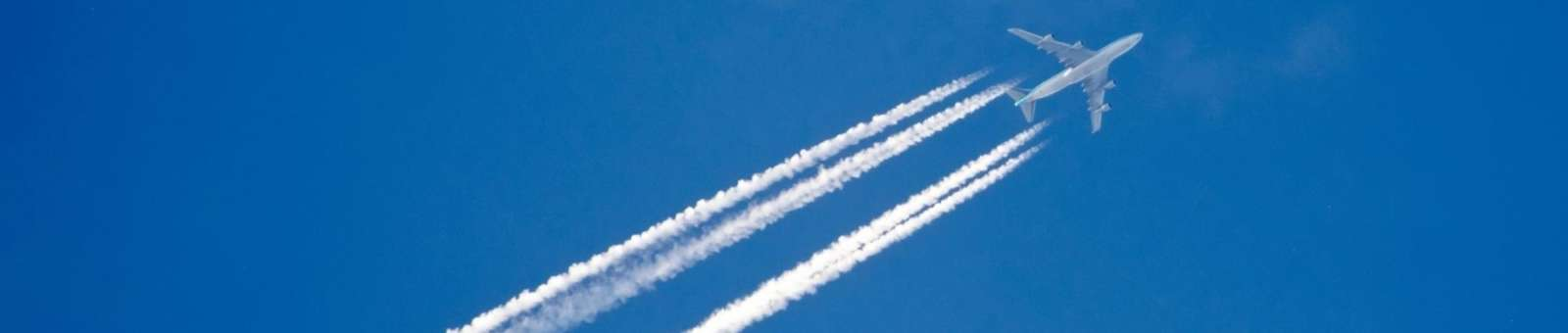 Contrails left behind by plane in flight takeoff launch sky is the limit banner