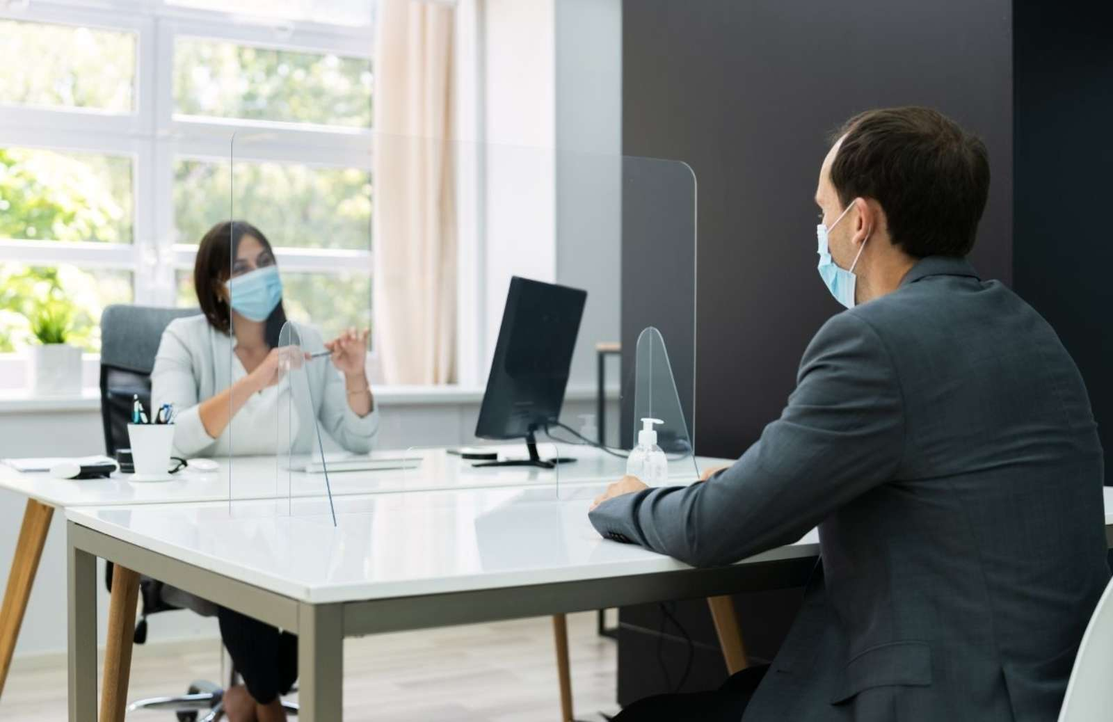 Woman and man sitting across a table from each other wearing medical masks