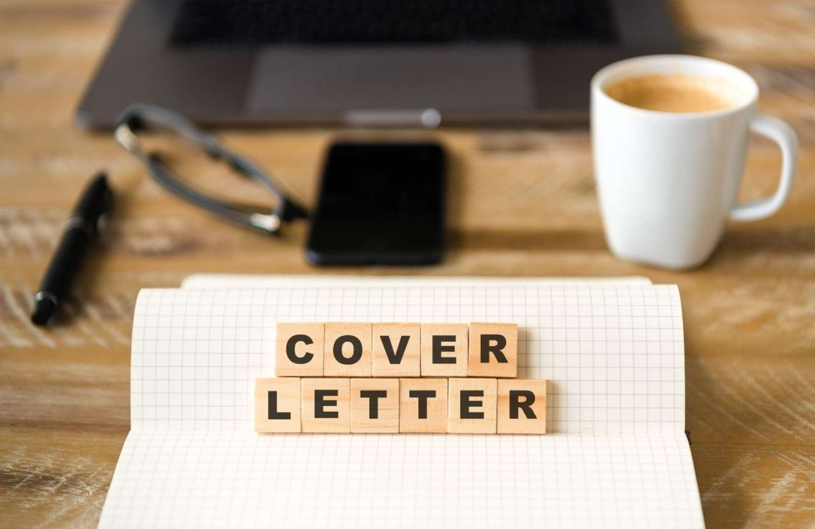 Desk top with the words COVER LETTER spelled out in tiles
