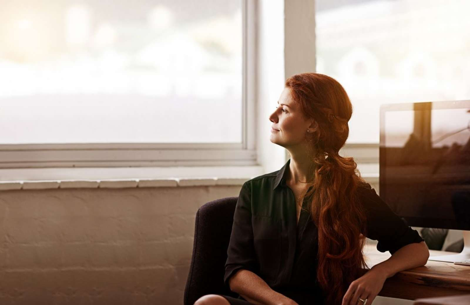 Woman sitting at a desk looking out of a window