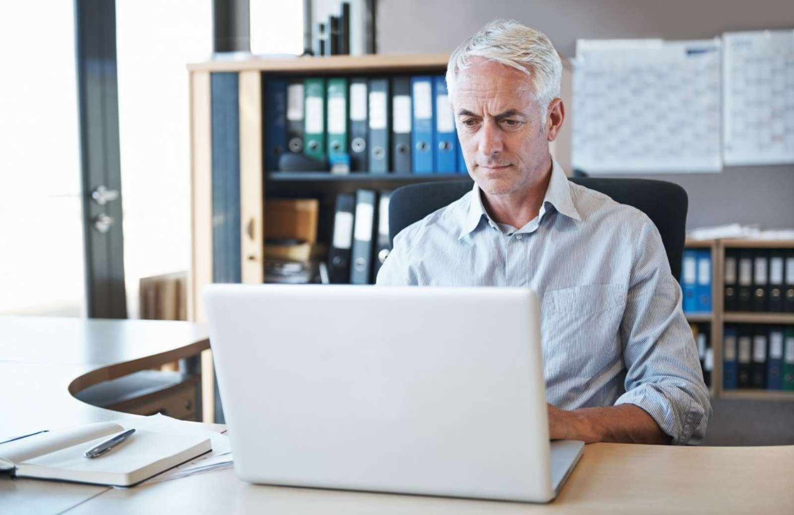 Gray-haired man sitting at desk working on a laptop computer