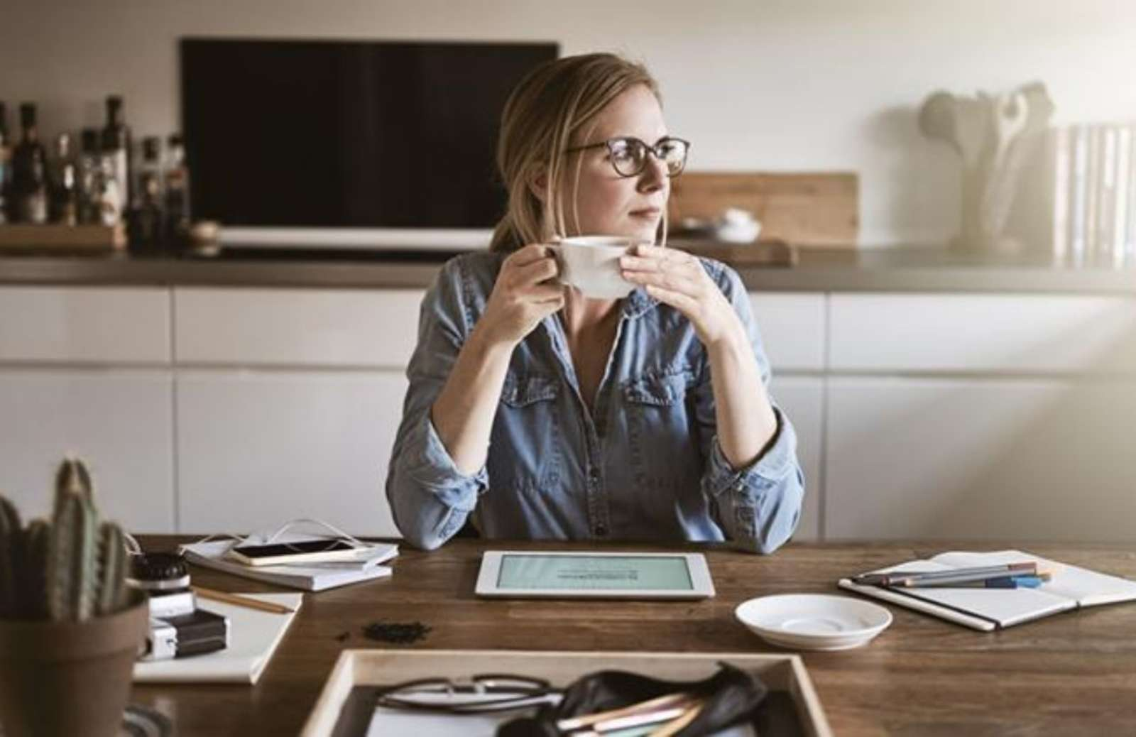 Woman sitting at desk, holding coffee mug and looking out of the window