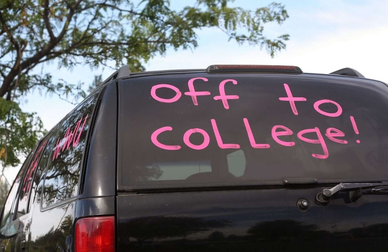 """Black SUV with the words """"off to college!"""" written in pink on window"""