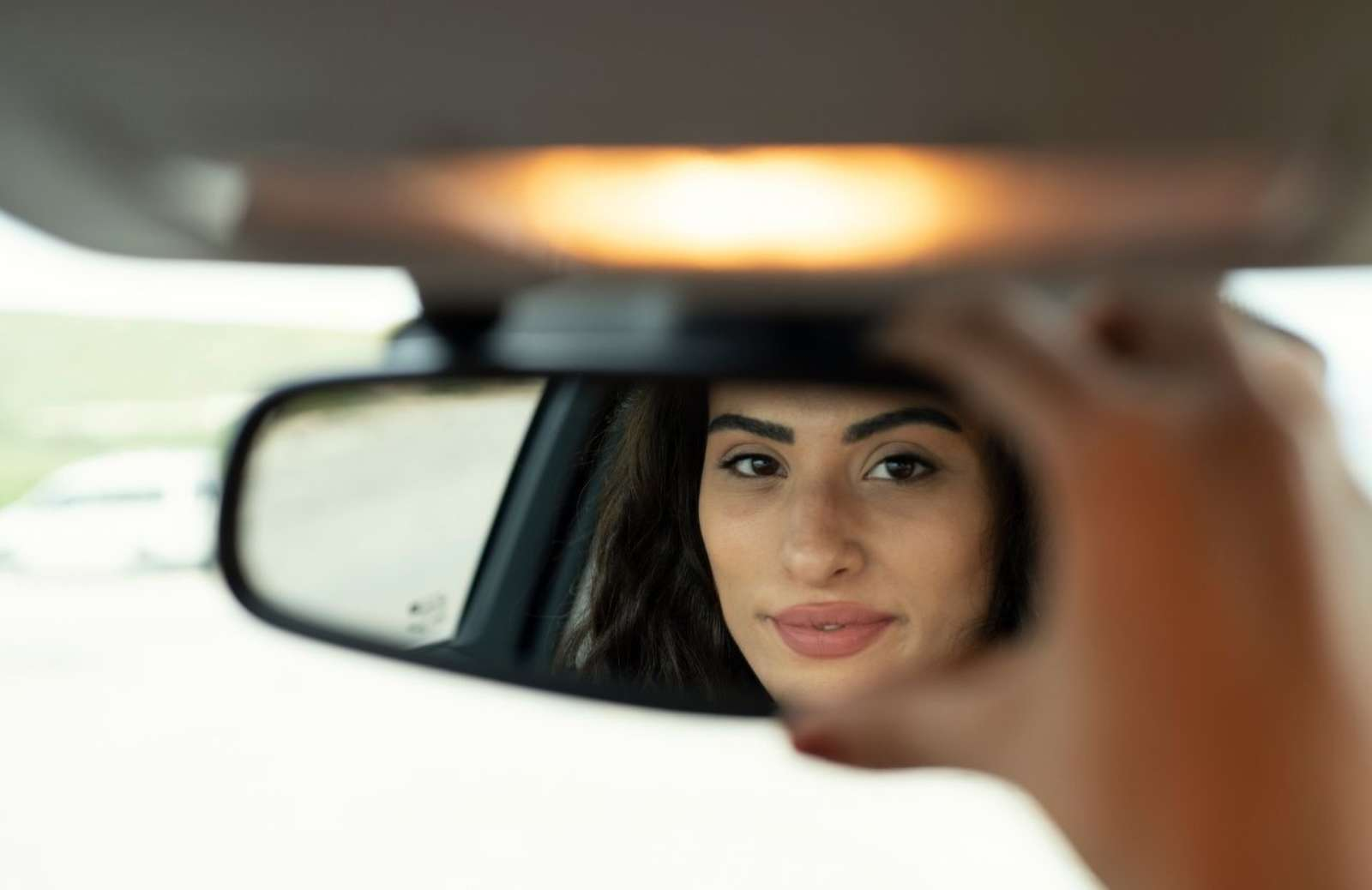 Woman smiling to herself as she adjusts rearview mirror in car