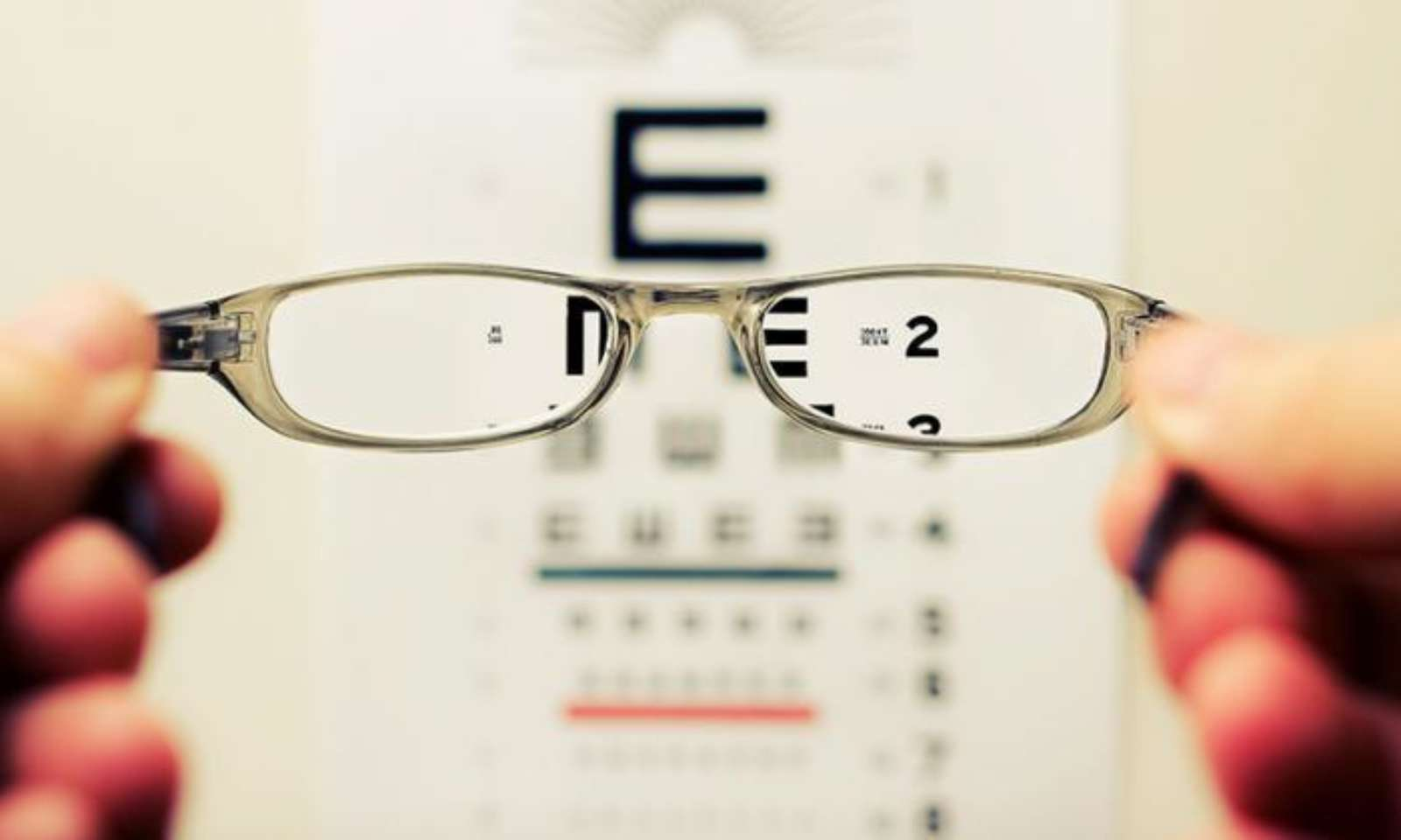 Vision chart with someone holding up glasses in foreground