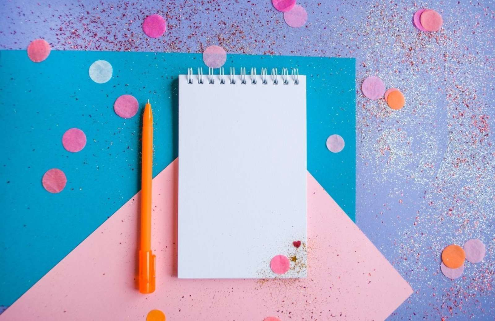 Blue and pink tabletop with spiral notebook and pencil