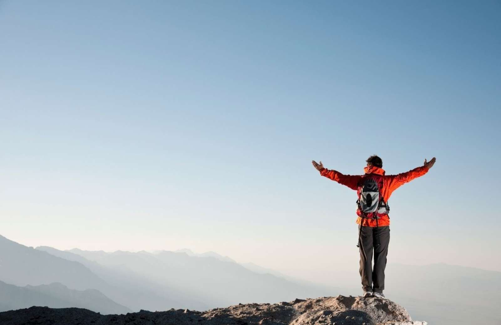 Person standing on mountain summit with outstretched arms