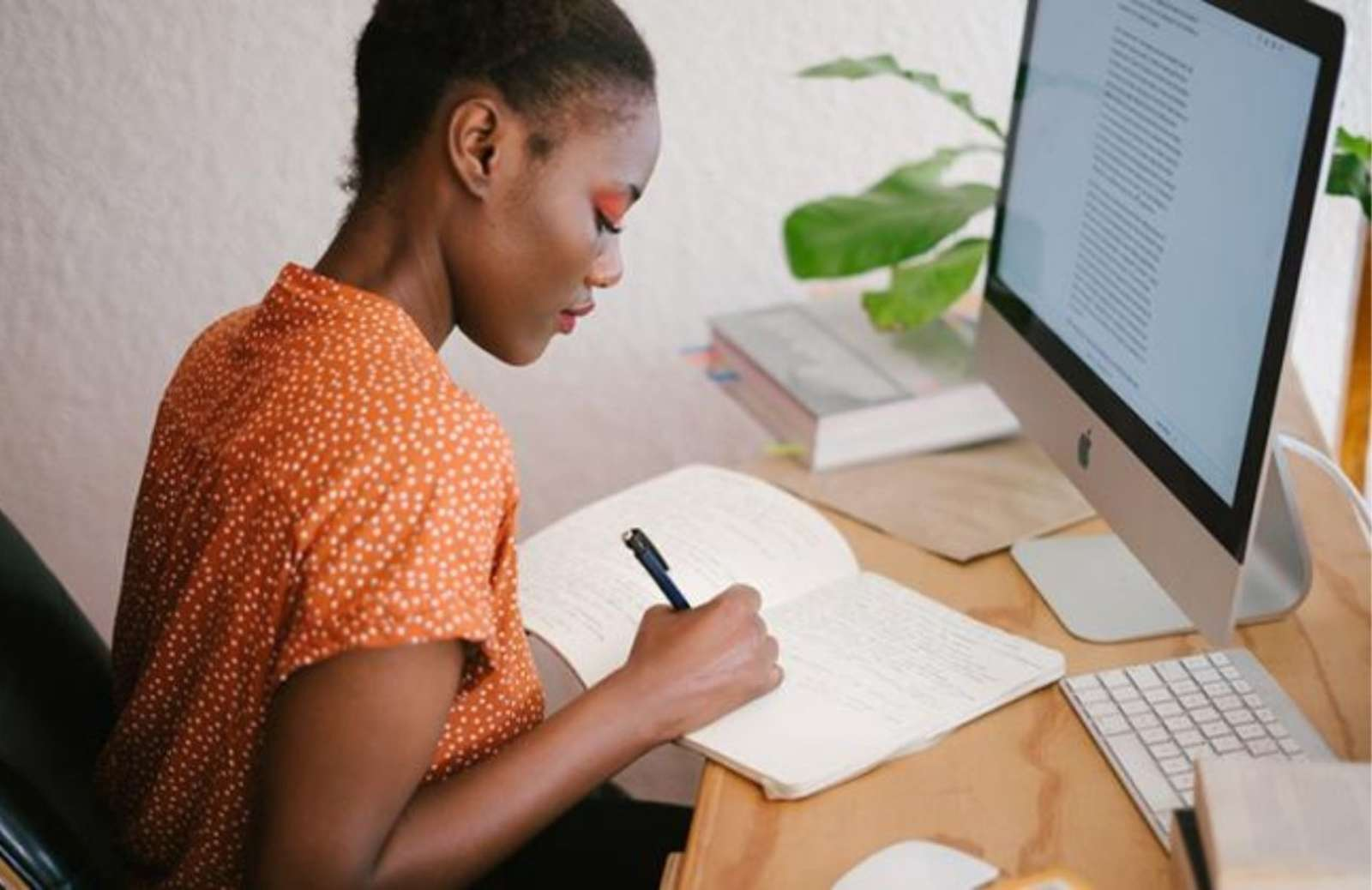 Woman taking notes at desk in front of computer screen