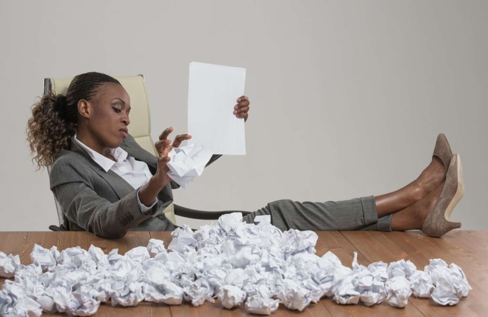 Business woman sitting with feet up on desk covered with balled-up paper