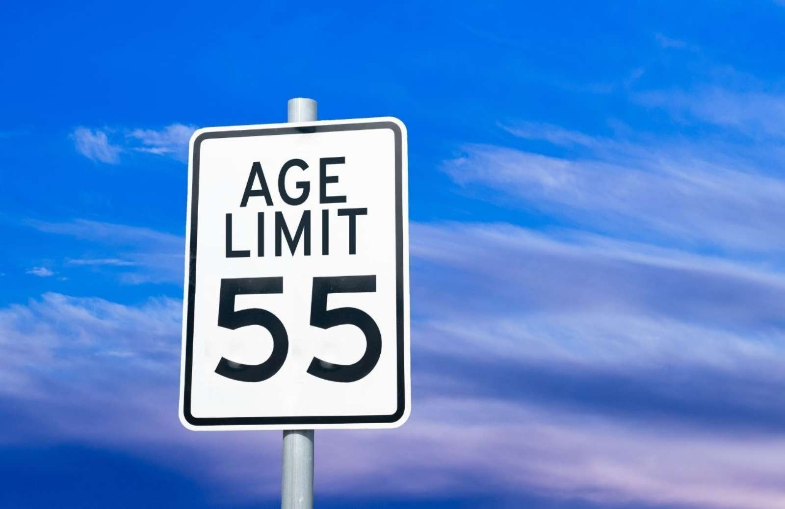 """Street sign reading """"Age Limit 55"""" against a blue sky"""