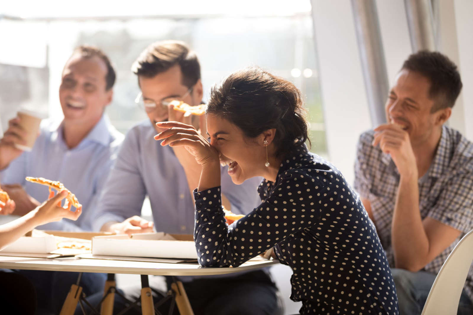 Laughing colleagues eating pizza group meeting work office setting