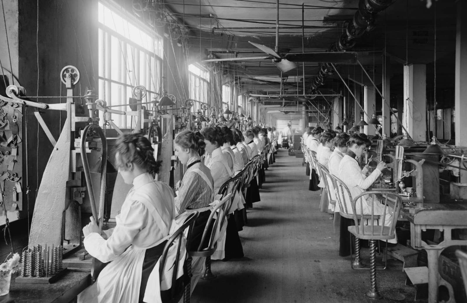 Vintage image of women in workshop assembly line sewing on antique machines