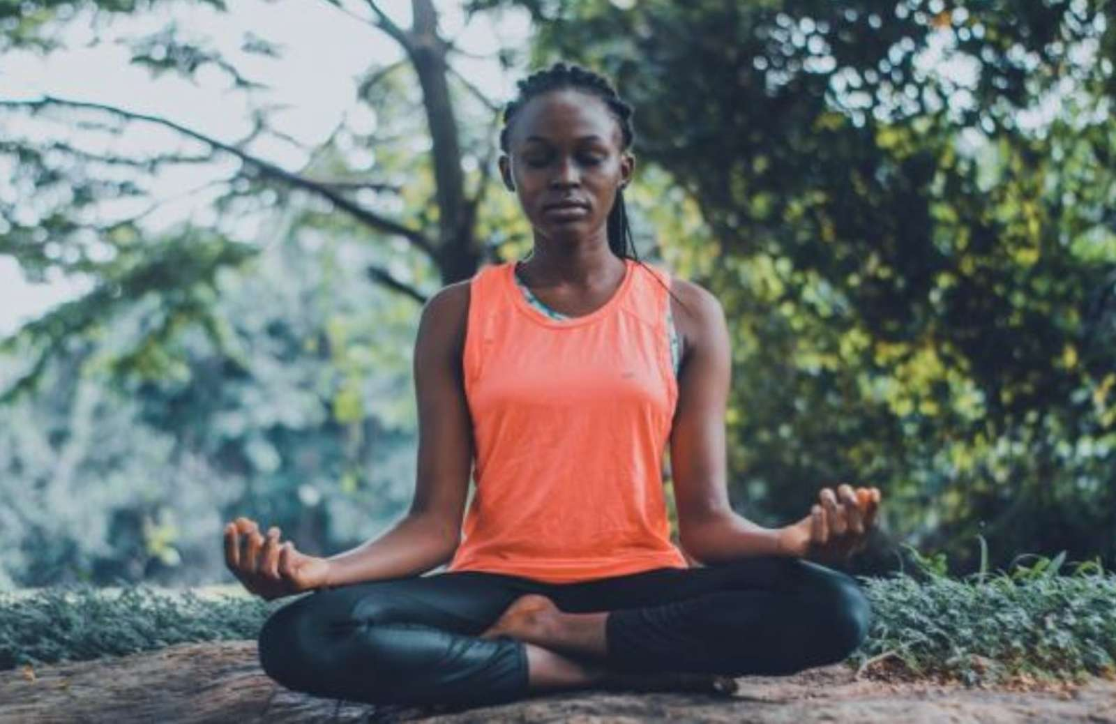 Woman sitting outside on ground practicing yoga