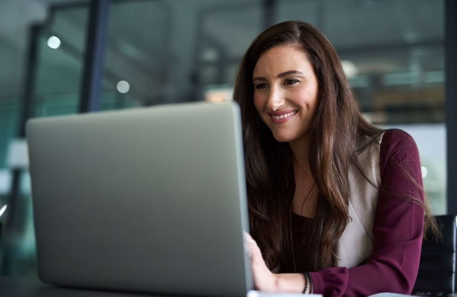 Woman smiling as she looks at laptop computer screen