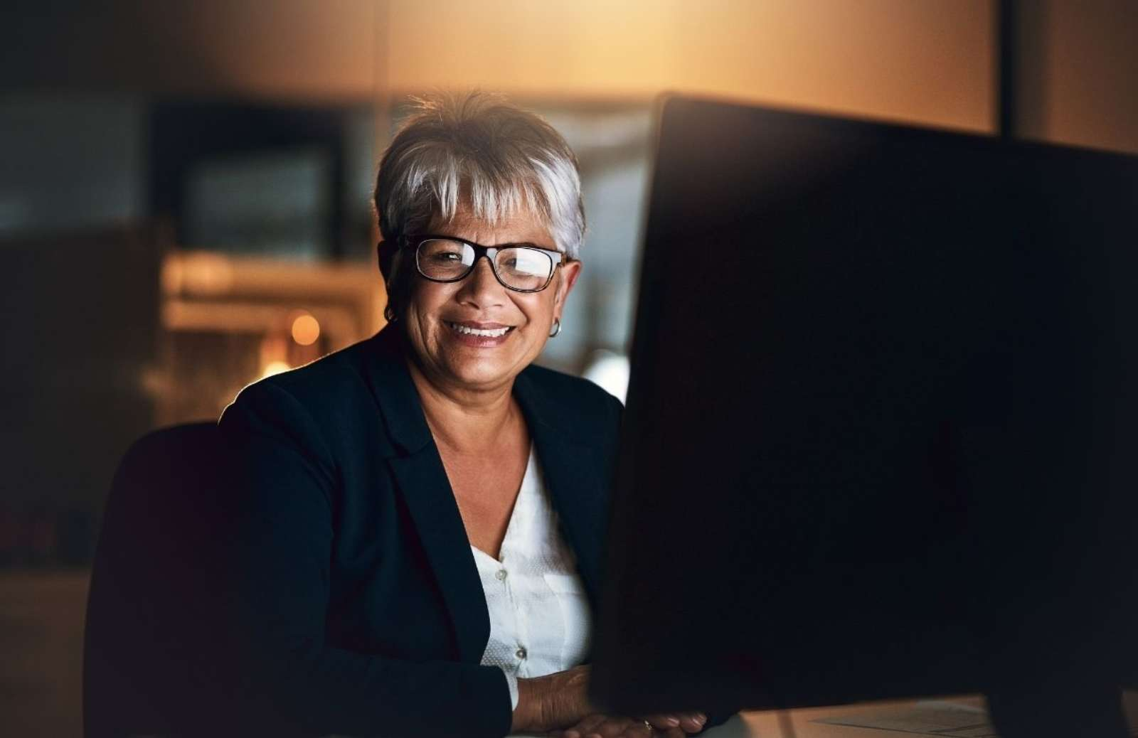 Woman sitting at desk smiling at camera while working on computer