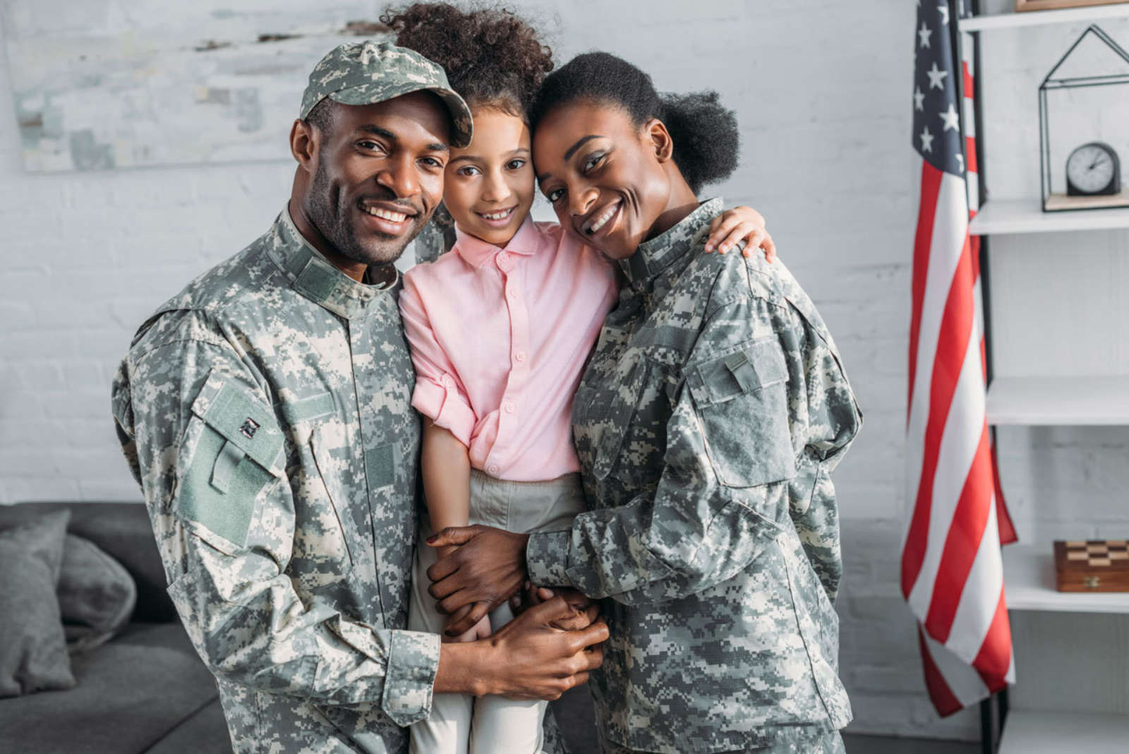 Military spouses family embracing daughter smiling hugging