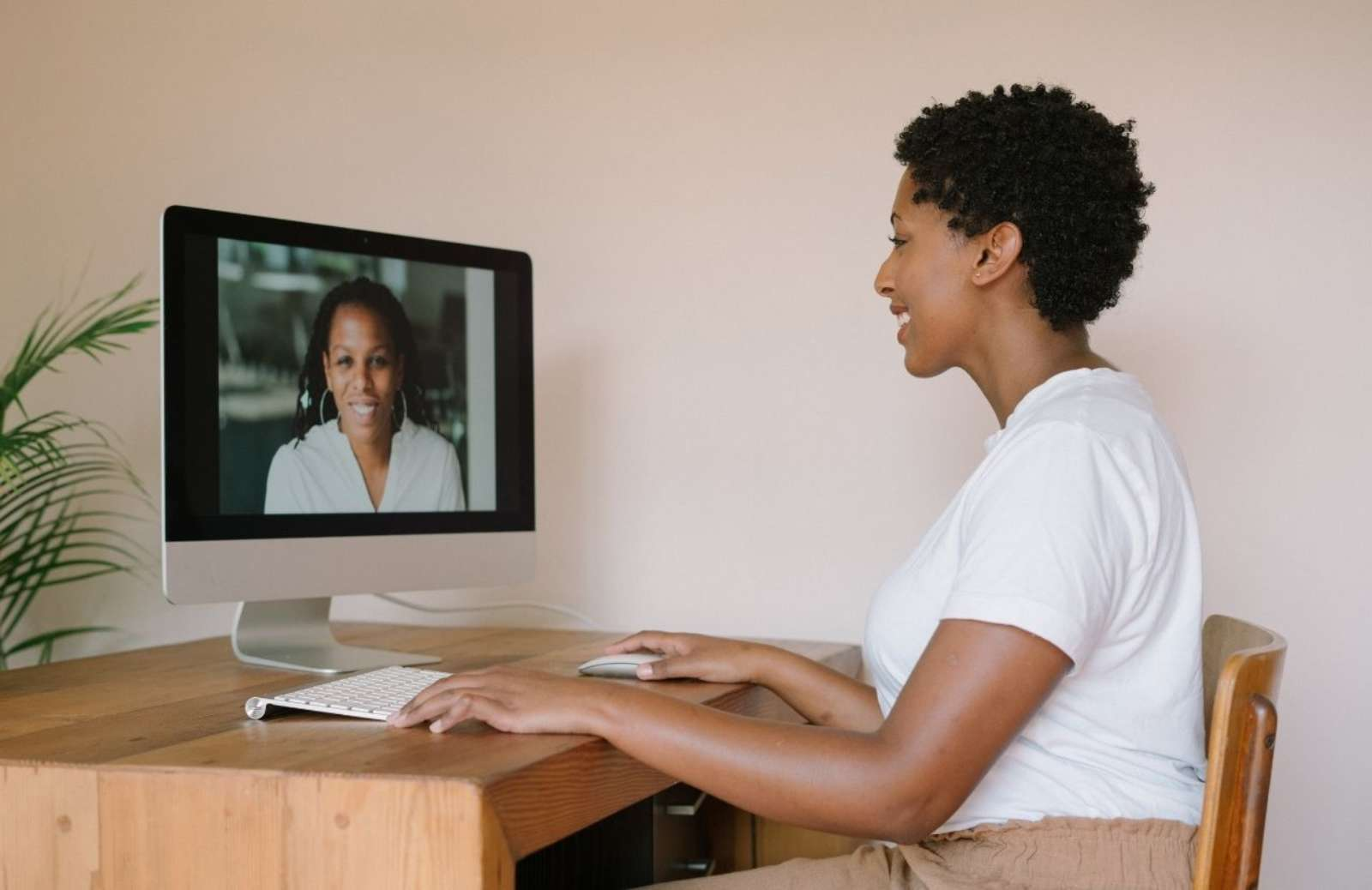 Woman at desk talking to another woman on her computer screen during virtual meeting