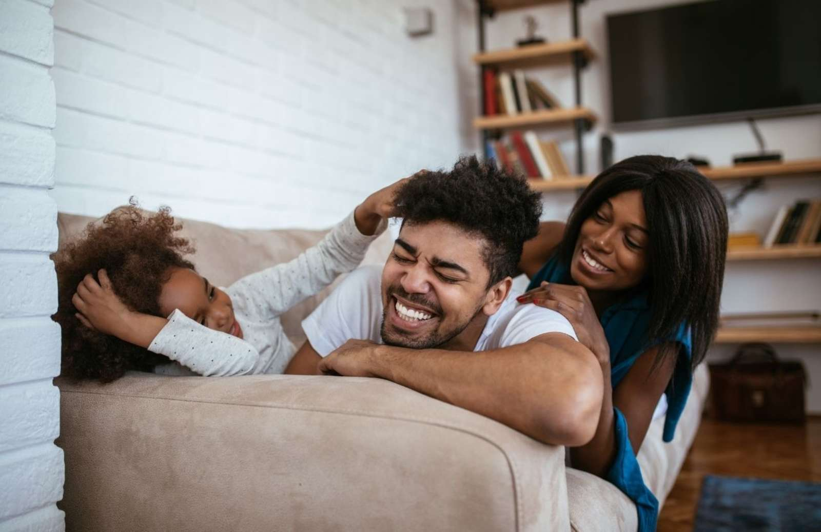 Young family laughing and cuddling on sofa