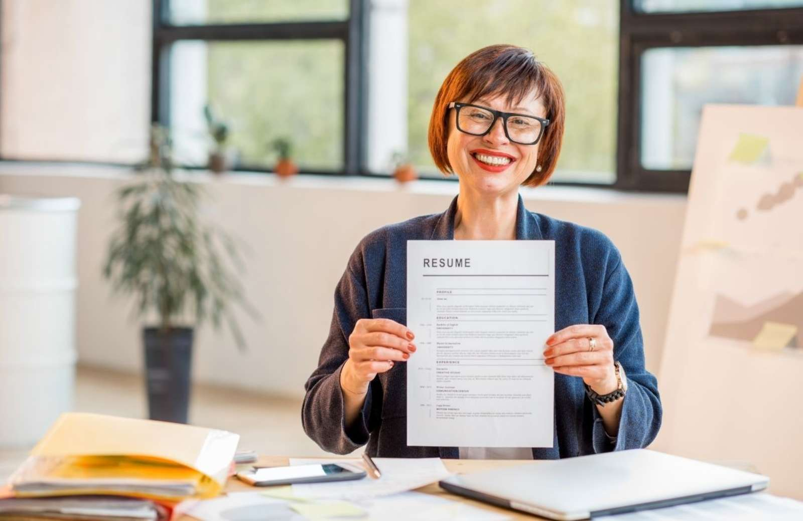 smiling woman holding up resume