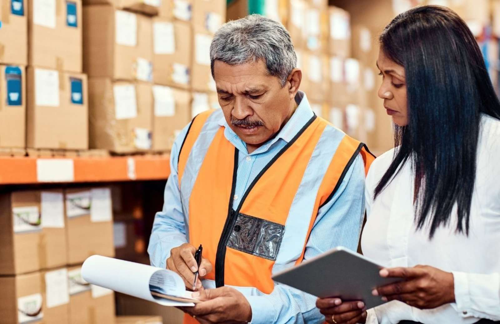 Warehouse man and woman holding tablet and paper and discussing their contents
