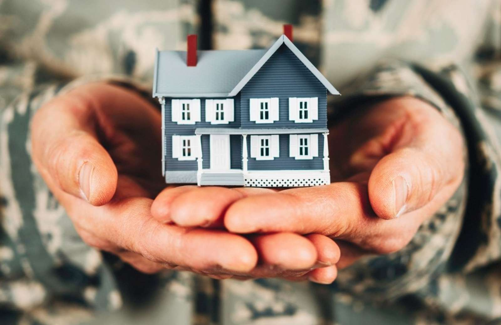 Person dressed in  military fatigues holding tiny house replica in palms