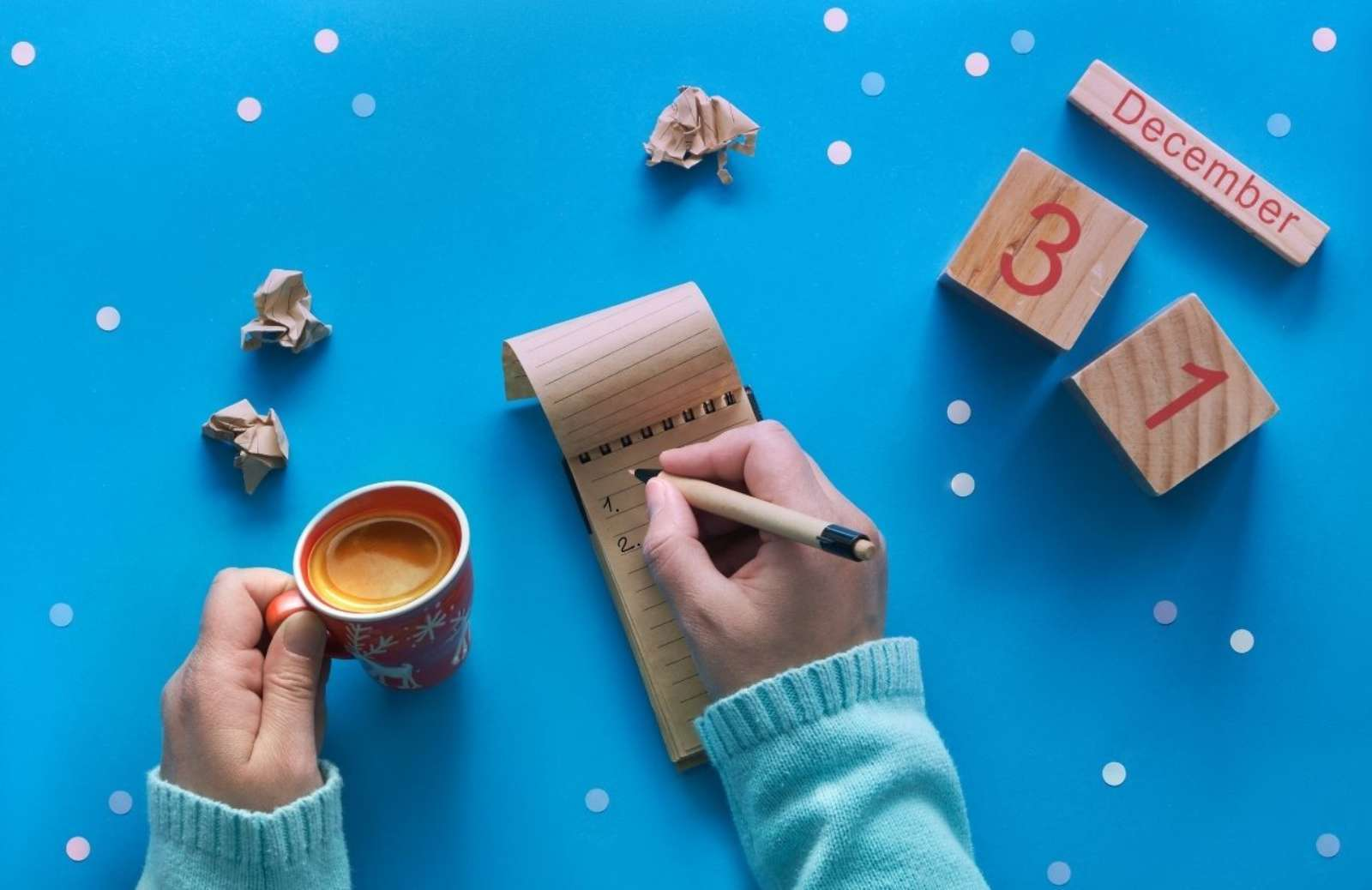 person writing on small pad of paper while holding coffee mug