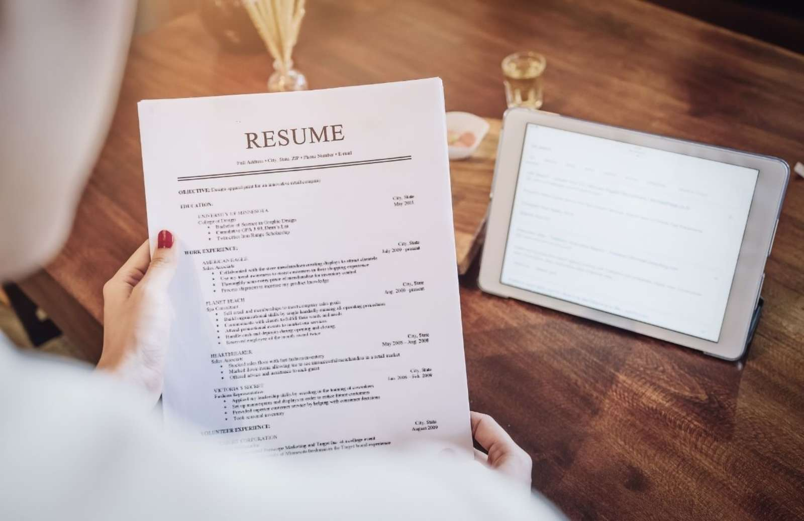 Person holding resume over desk with tablet