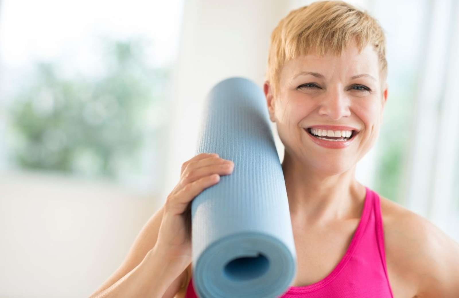 Smiling woman holding rolled-up yoga mat