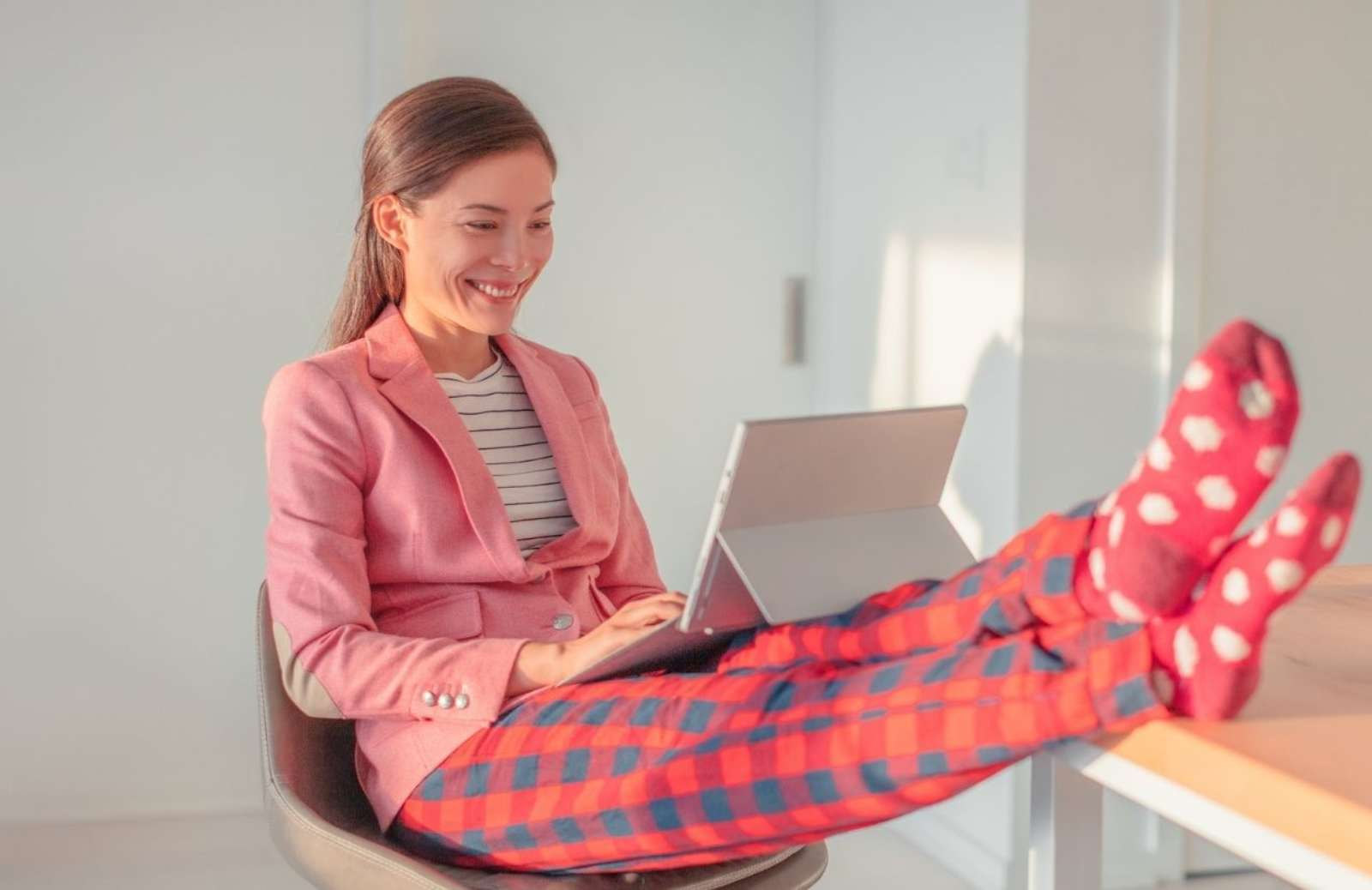 Woman with feet on desk, wearing pajamas, smiling while working on laptop computer