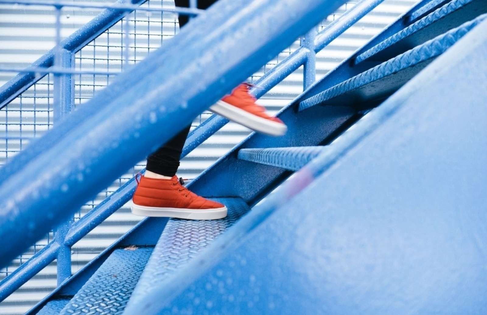 Person in red hig-top tennis shows ascending blue staircase