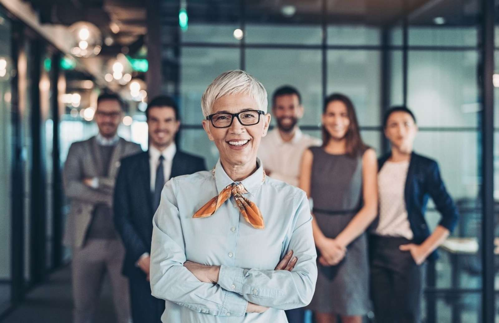 Smiling mature woman in office with coworkers in line behind her at work