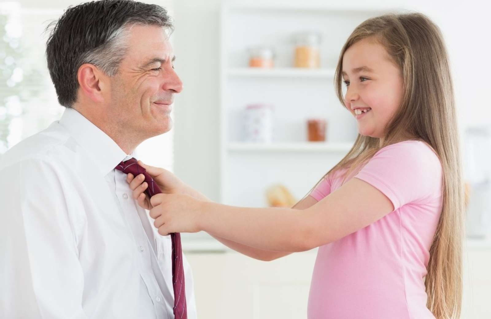Professional man smiling while young daughter ties his tie