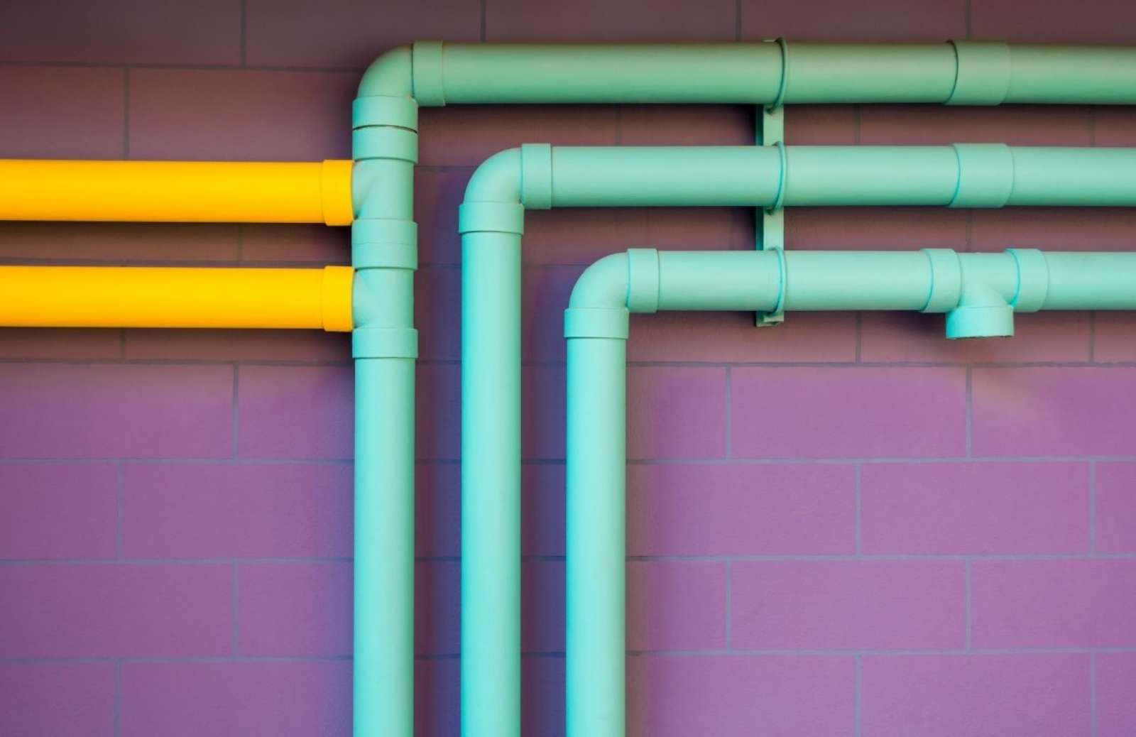 Teal and yellow pipelines against purple brick wall