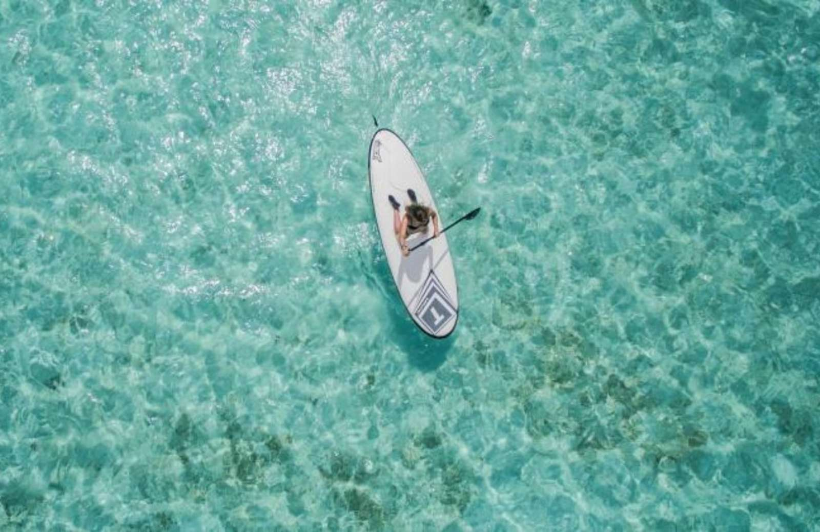 Aerial image of person on paddleboard in turquoise water